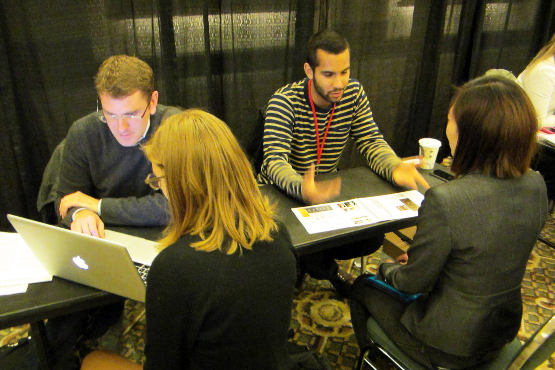 A photo of four people seated at a table looking at a computer and papers