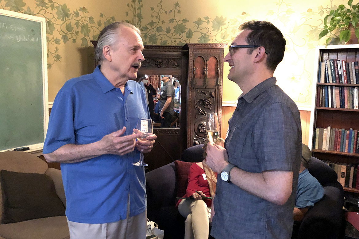 Photo of two alumni in conversation with drinks.