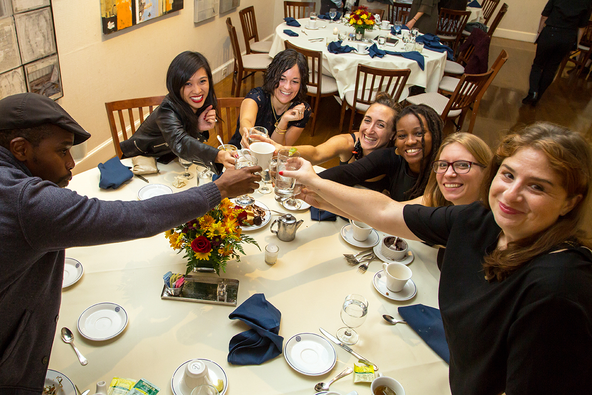Photo of alumni, seated around a table, clinking glasses