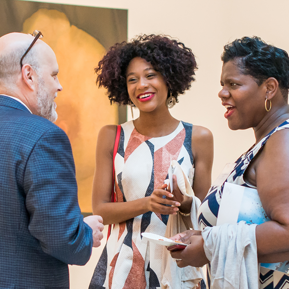 Photo of two women talking and laughing with an alumnus at a send-off reception.