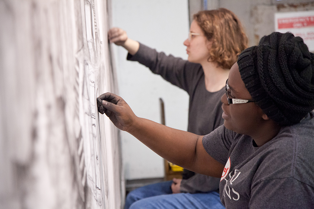Photo of two students working with charcoal.
