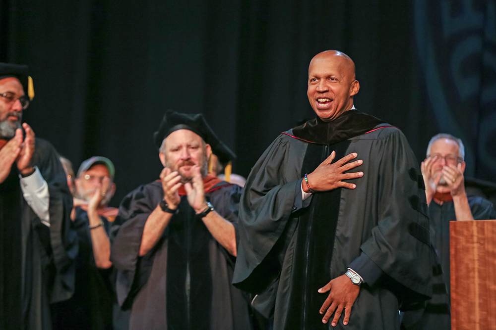 Faculty applaud fellow member on graduation stage.