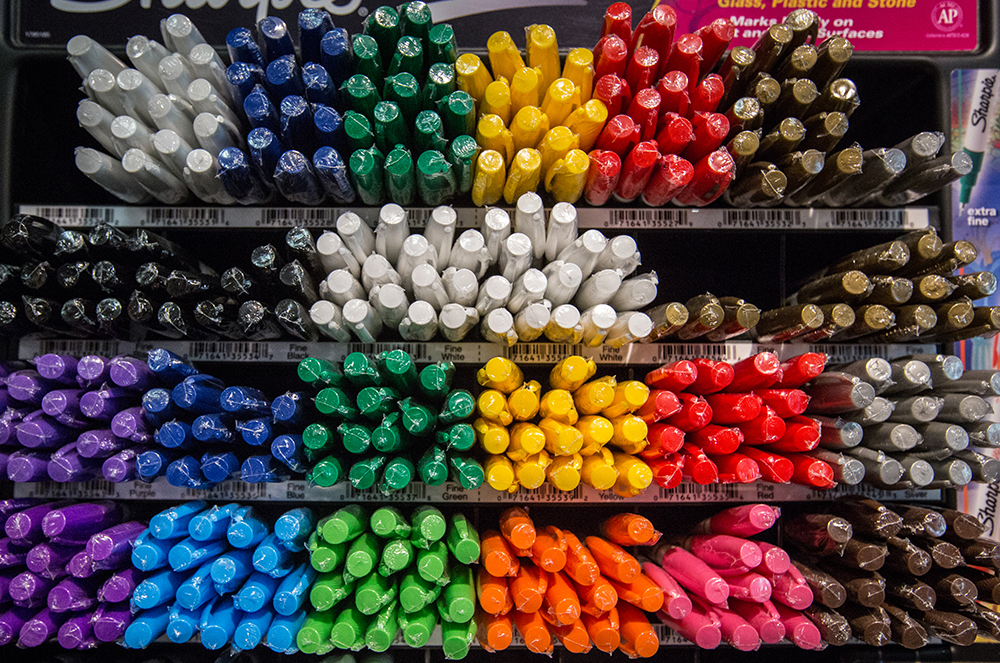 Colorful photo of markers bunched by color.