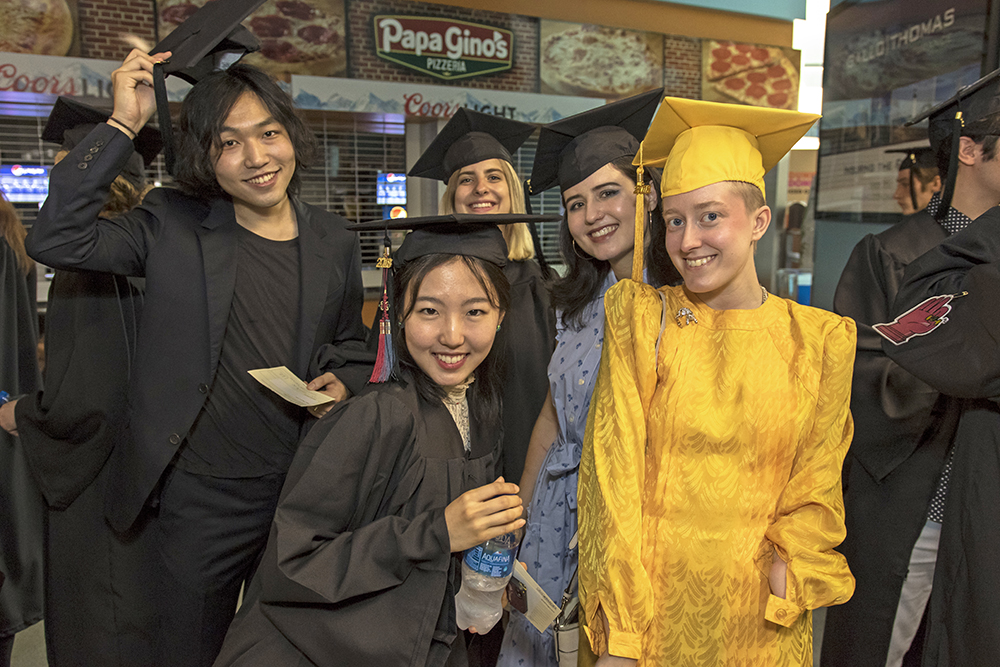 Group of students in caps and gowns - one student in all gold.