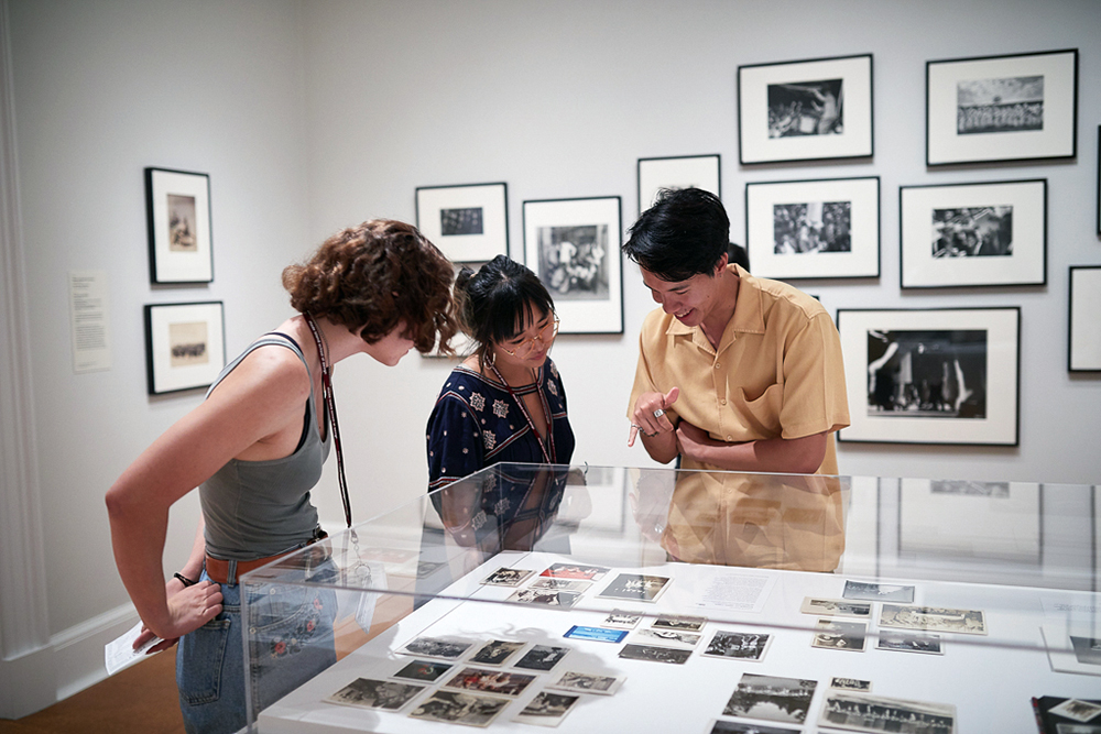 Students looking at photographs in a display at RISD Museum.