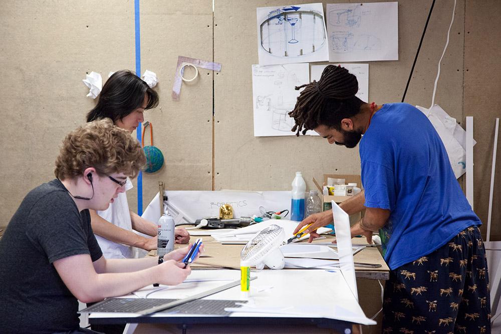 Photo of three students working on a project.