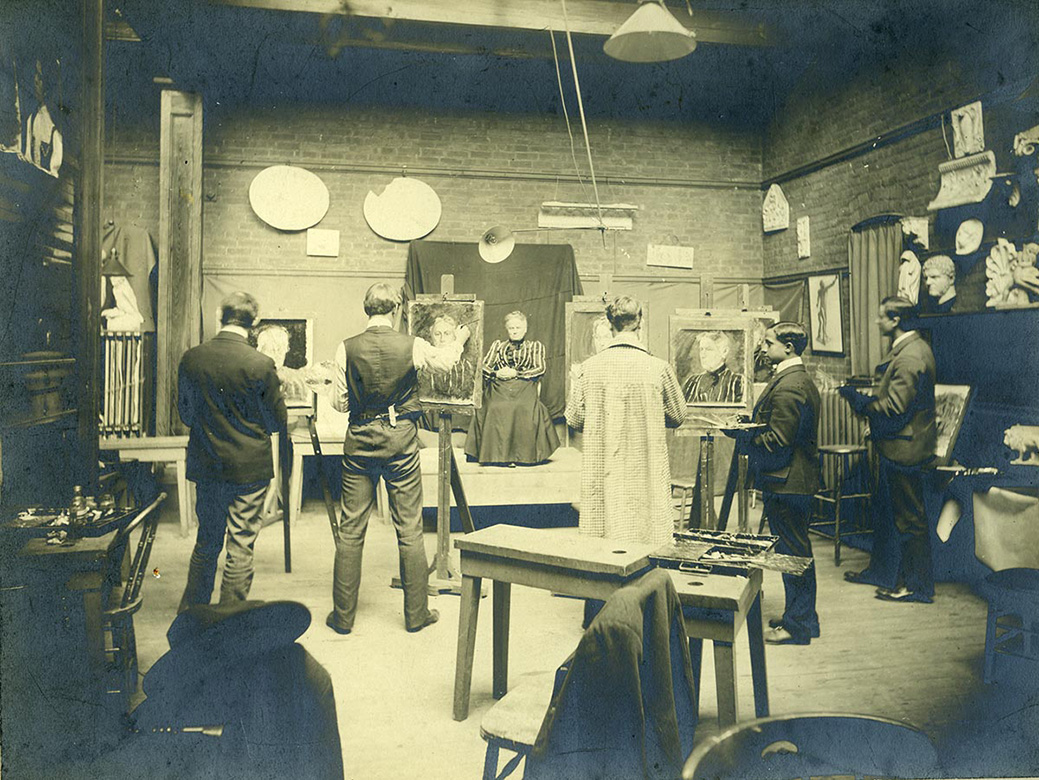 Historic 19th century photo of students painting in a studio.
