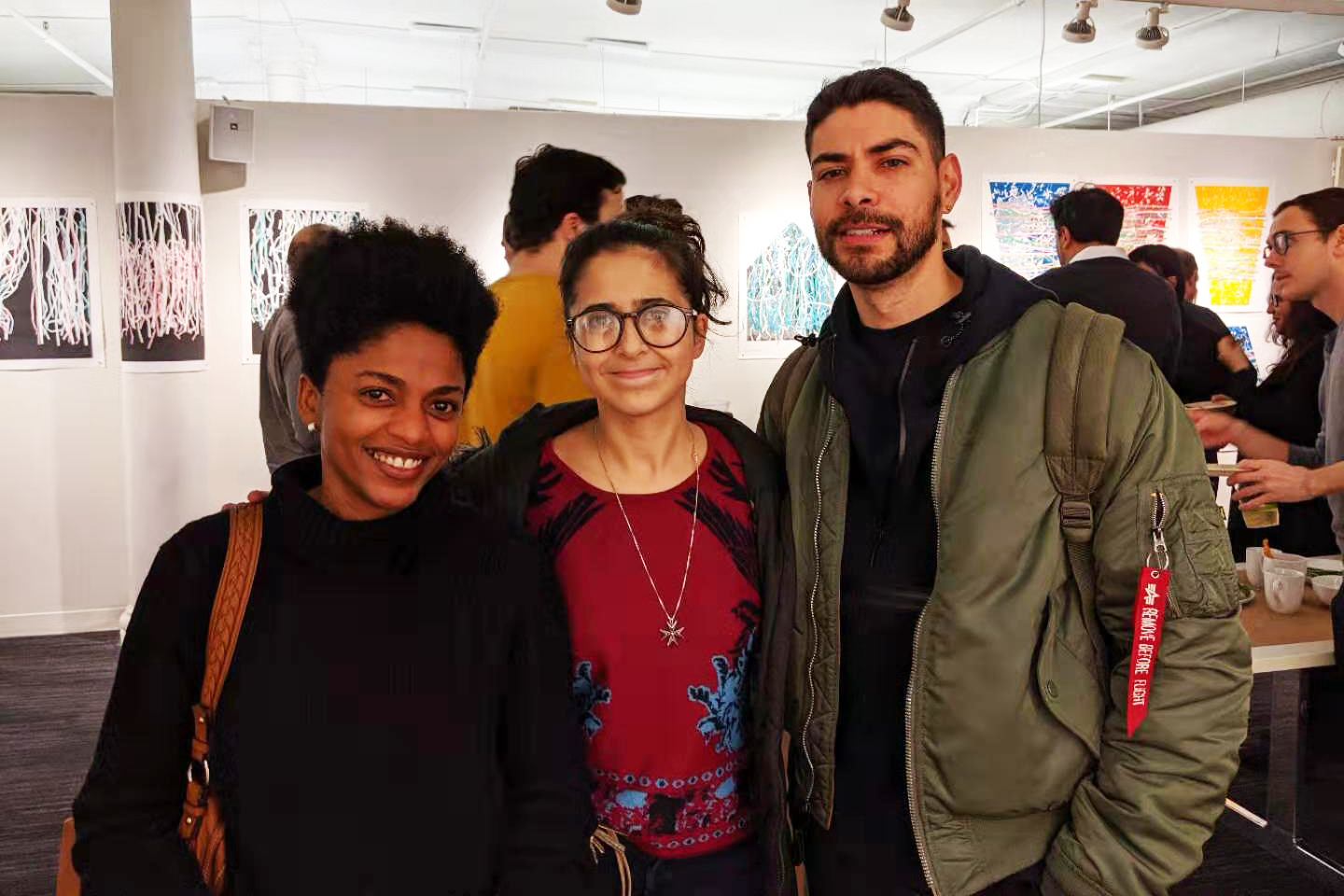Photo of three alumni standing in a gallery space.