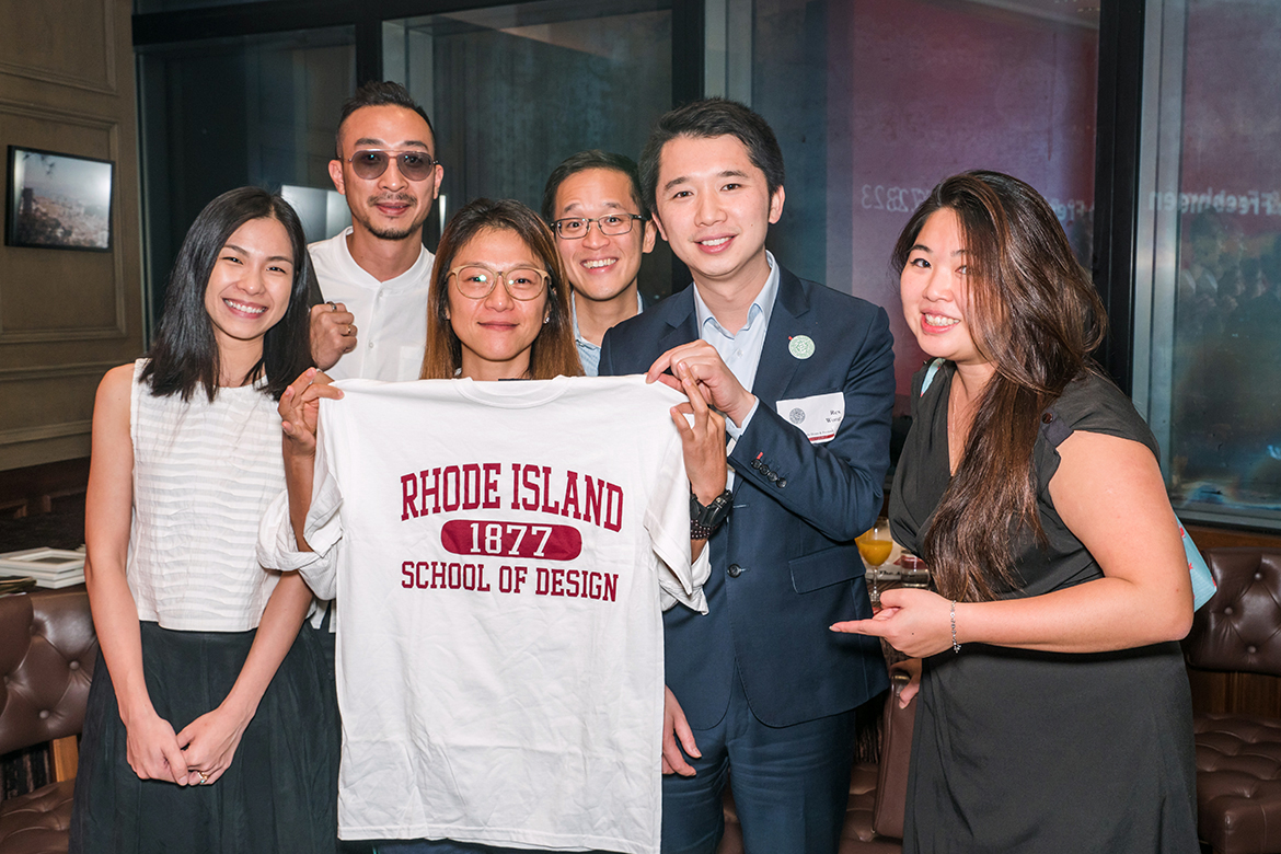 Members of the RISD Club of Hong Kong posing and holding a RISD t-shirt.
