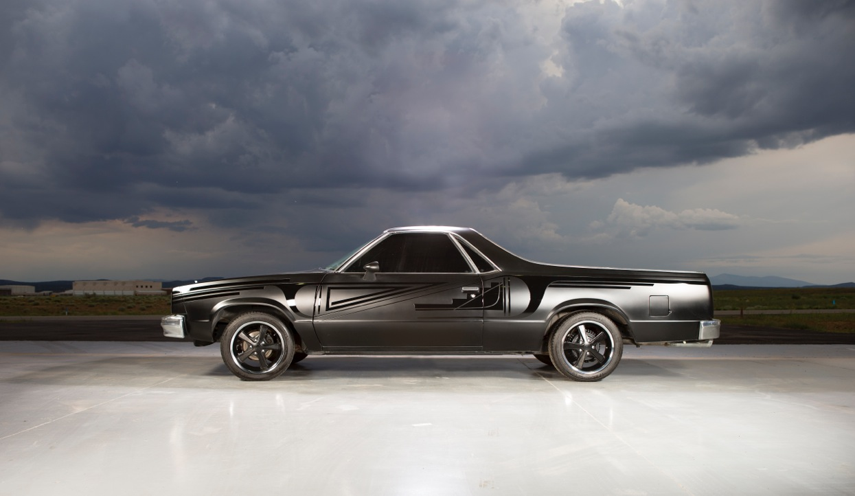 Image of a black and grey an El Camino under a cloudy sky